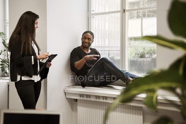 Giovani colleghi e colleghe che discutono del lavoro in carica — Foto stock