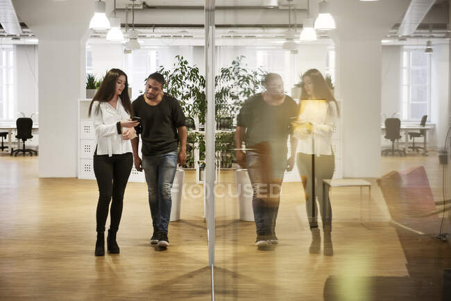 Coworkers using smartphone by window in office, full length view — Stock Photo