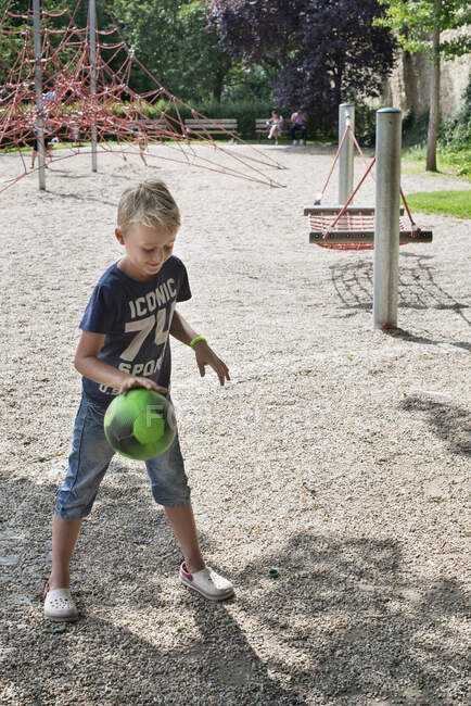 Boy bouncing ball on playground at sunny day — Stock Photo