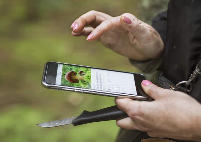 Woman using smart phone, mushrooms on screen — Stock Photo