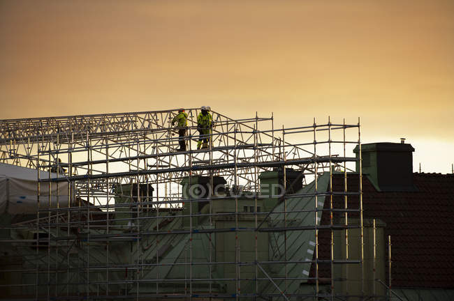 Construction workers on scaffolding at sunset — Stock Photo