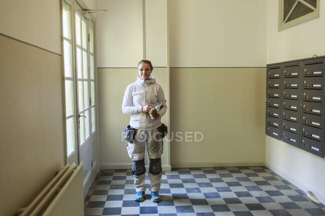 Painter standing by mailboxes and looking at camera in apartment building — Stock Photo