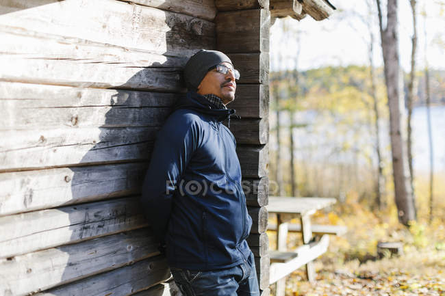 Man wearing beanie and jacket leaning on log cabin — Stock Photo