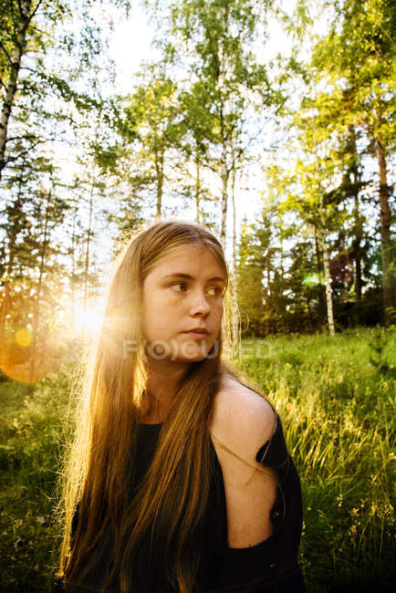 Portrait of young woman in forest at sunset — Stock Photo