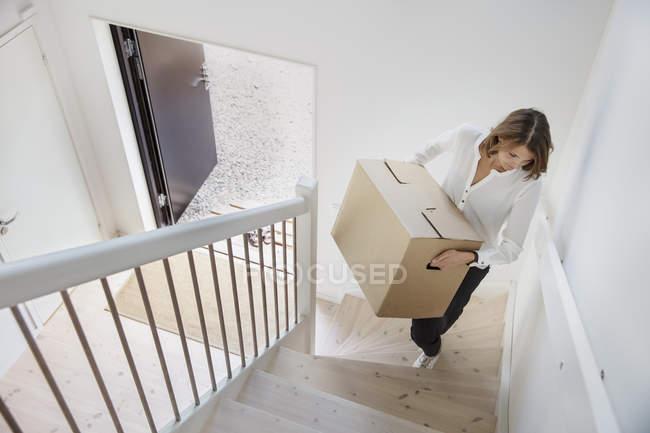 Женщина с картонной коробкой на лестнице — стоковое фото