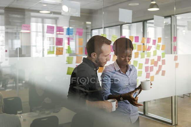 Selektiver Fokus multiethnischer Mitarbeiter mit Tassen und Smartphone im Büro — Stockfoto