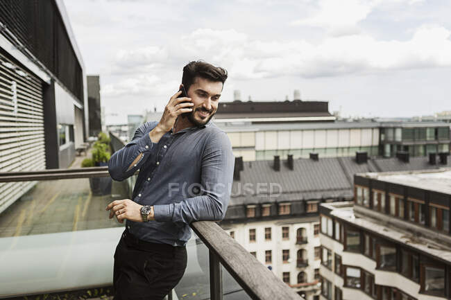 Young man talking on cell phone on balcony — Stock Photo
