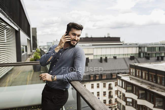 Jeune homme parlant au téléphone cellulaire sur un balcon — Photo de stock