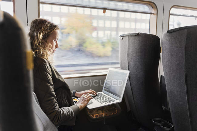 Young woman traveling on train using laptop — Stock Photo