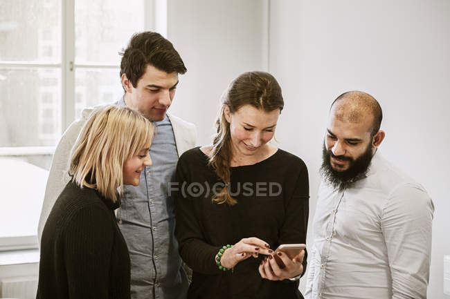 Coworkers guardando smart phone — Foto stock
