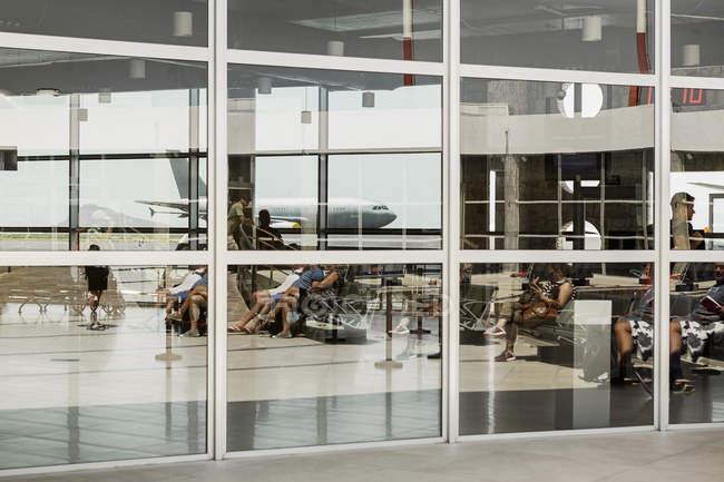 Самолет отражается в окне в аэропорту — стоковое фото