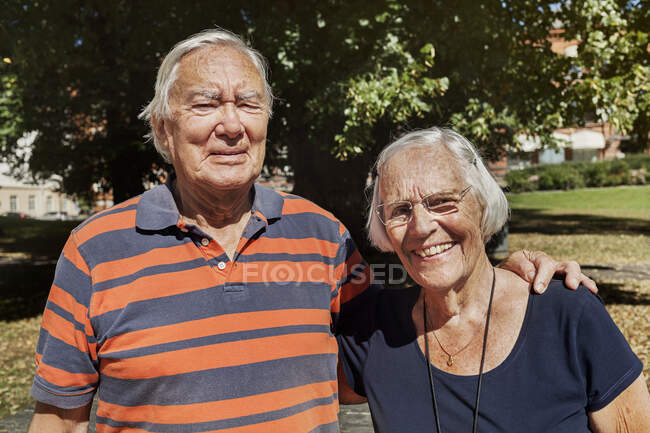 Portrait of happy senior couple standing together outdoors at sunny day — Stock Photo