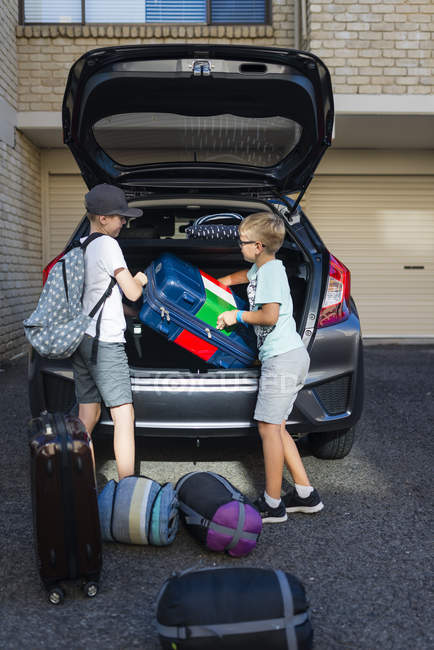 Boys unloading suitcase from car boot — Stock Photo