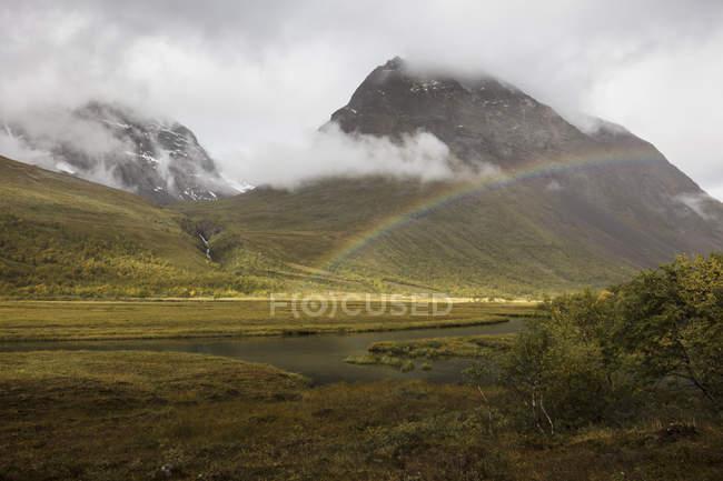Arco-íris em frente às montanhas em Norrbotten, Suecia — Fotografia de Stock