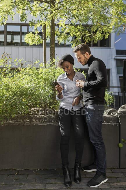 Des amis regardent un téléphone intelligent dans la rue — Photo de stock