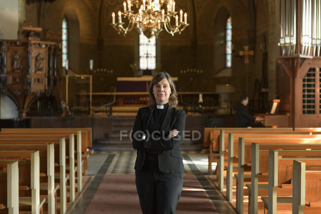 Portrait of priest standing with crossed arms and looking at camera in church — Stock Photo
