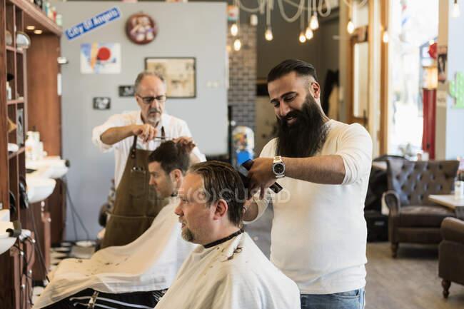 Peluqueros cortando el pelo de los clientes en la barbería - foto de stock