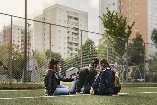 Девочки-подростки используют смартфон на теннисном корте — стоковое фото