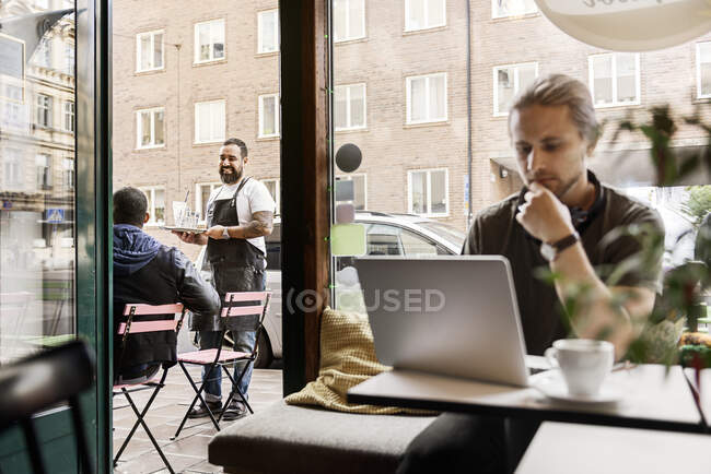 Barista serving young man at outdoor cafe table — Stock Photo