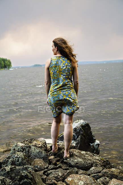 Vue arrière d'une femme debout sur des rochers et vue de la mer — Photo de stock