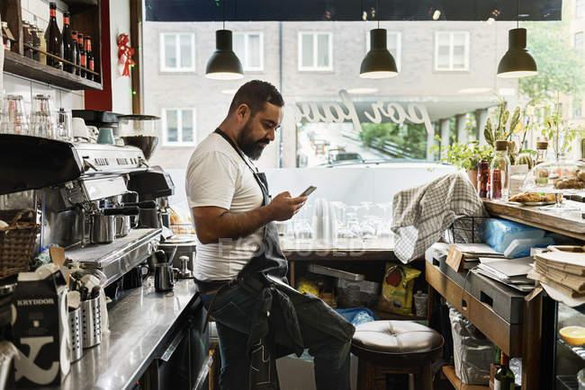 Взрослый мужчина работает в кафе, используя смартфон — стоковое фото