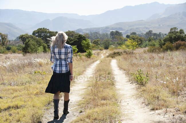 Vue arrière de la femme marchant sur un chemin de terre au Cap, Afrique du Sud — Photo de stock