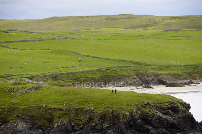 Falaise herbeuse avec des silhouettes de deux personnes sur les îles Shetland, Royaume-Uni — Photo de stock