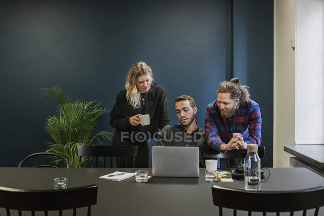 Coworkers looking at laptop, selective focus - foto de stock