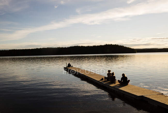 Young women sitting on wooden pier of a lake in Dalarna, Sweden — Stock Photo