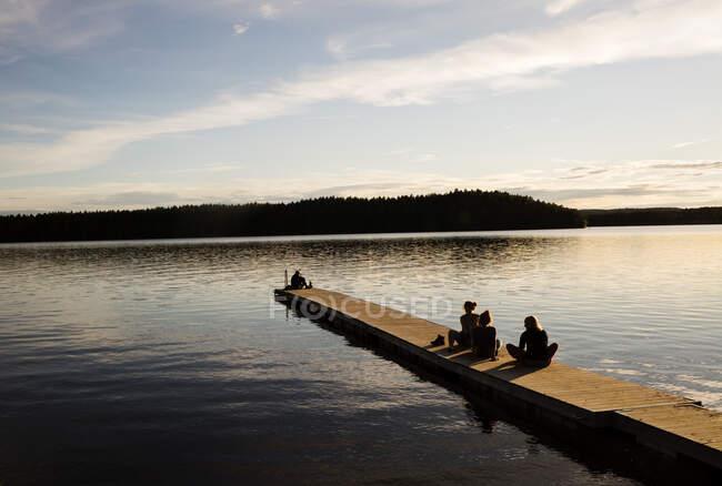Mujeres jóvenes sentadas en un muelle de madera de un lago en Dalarna, Suecia. - foto de stock