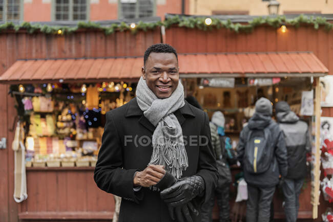 Portrait of young man smiling at camera while standing at market — Stock Photo