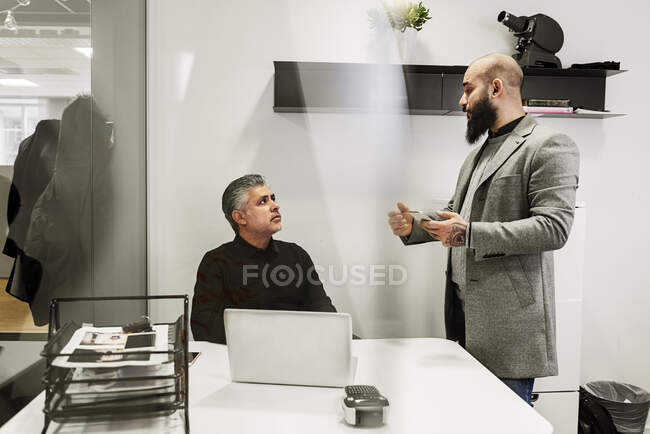 Serious businessmen working and talking in office — Stock Photo
