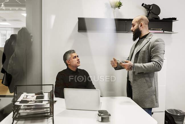 Seri uomini d'affari che lavorano e parlano in ufficio — Foto stock