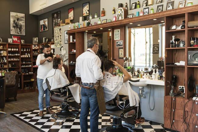 Парикмахеры стригут клиентам волосы, избирательно фокусируясь — стоковое фото