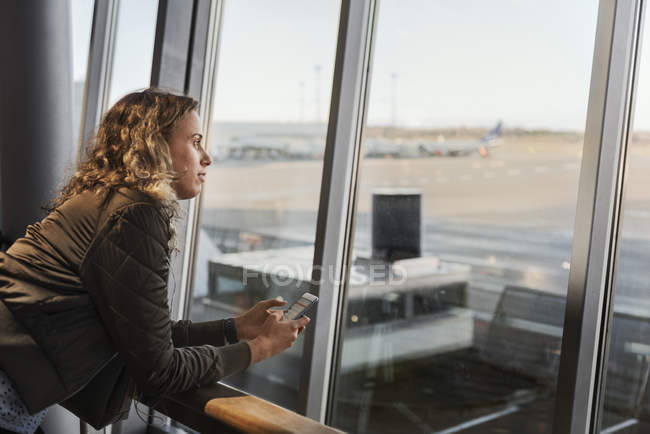 Woman with smart phone by airport window — Stock Photo