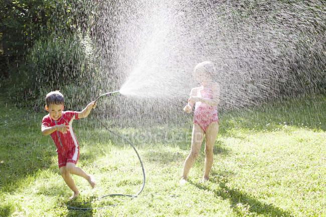 Irmão e irmã brincando com mangueira, foco seletivo — Fotografia de Stock
