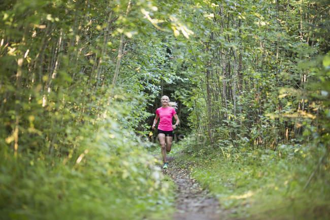 Mulher correndo na floresta, foco seletivo — Fotografia de Stock