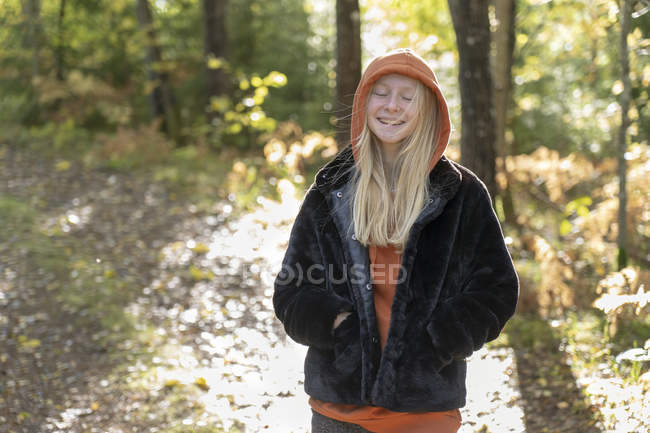 Smiling teenage girl with her eyes closed in forest — Stock Photo