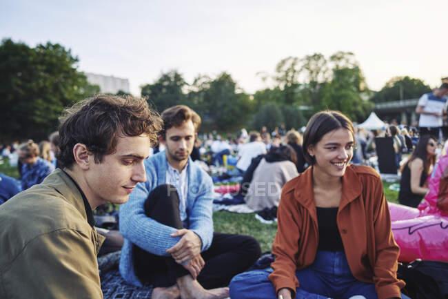Jóvenes amigos sentados juntos en el parque - foto de stock