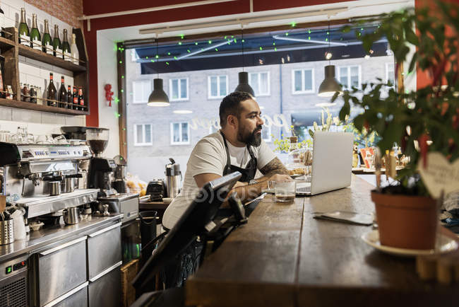Mid adult man working in cafe, using laptop — Stock Photo