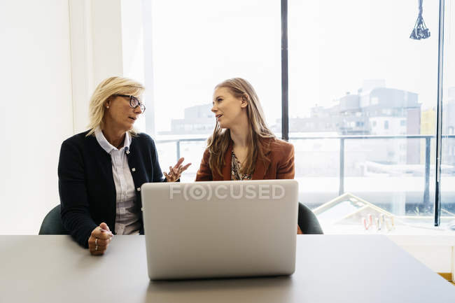 Businesswomen with laptop, focus on foreground — Stock Photo