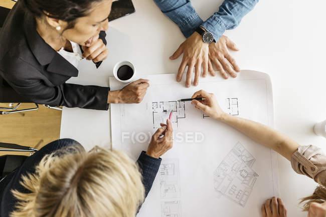 Les hommes d'affaires regardent les plans pendant la réunion — Photo de stock