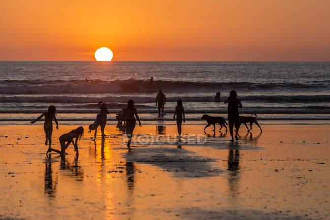 Силуэты людей на пляже на закате в Коста-Рике — стоковое фото