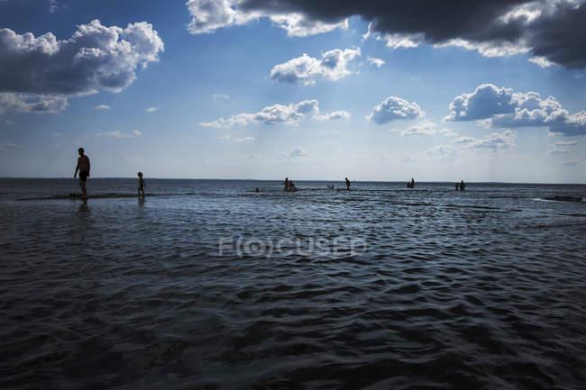 Siluetas de personas caminando a lo largo del mar bajo el cielo nublado - foto de stock