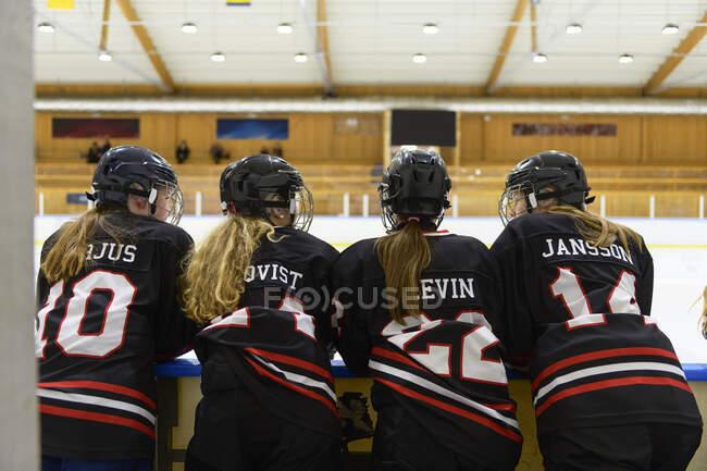 Girls in ice hockey uniforms beside ice rink — Stock Photo