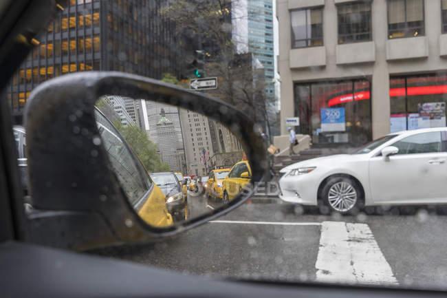 Отражения в боковом зеркале на городской улице — стоковое фото
