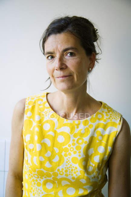 Портрет зрелой женщины у белой стены — стоковое фото