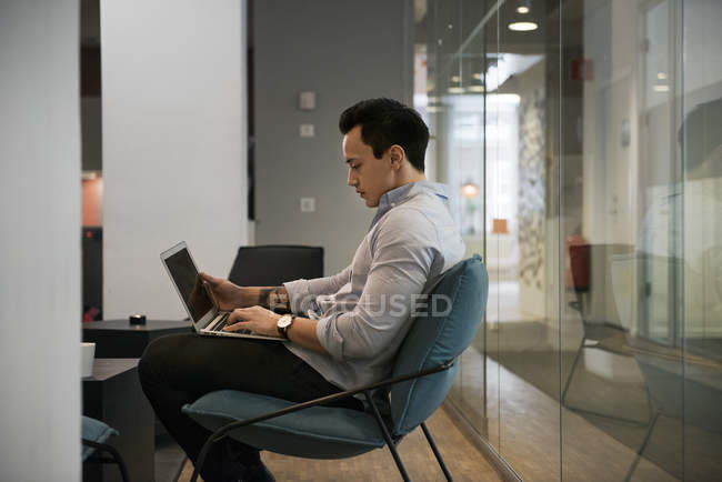 Hombre joven usando portátil, enfoque selectivo - foto de stock