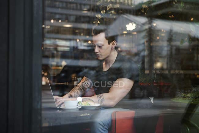 Молодий чоловік використовує ноутбук за вікном, селективний фокус. — стокове фото