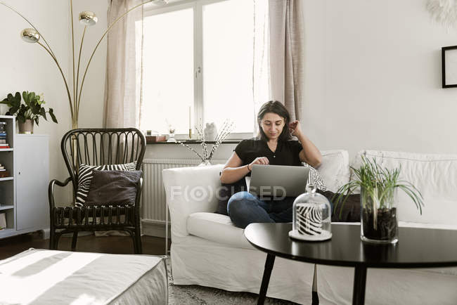 Young woman using laptop on sofa — Stock Photo
